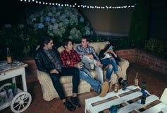 Jeunes hommes parlant et buvant en partie Images stock