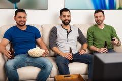 Jeunes hommes regardant la TV à la maison Image stock