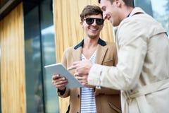 Jeunes hommes riants à l'aide de la Tablette dehors Photo stock