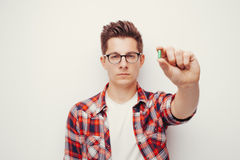 Jeunes hommes sérieux dans la chemise rouge tenant une certaine main de pilule Images libres de droits