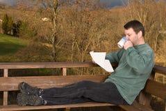 Jeune homme avec du café et le journal Photographie stock libre de droits