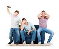 Jeunes hommes s'asseyant sur un sofa déçu Photographie stock libre de droits