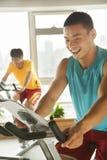 Jeunes hommes sur les vélos stationnaires s'exerçant dans le gymnase Photographie stock libre de droits