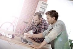 Jeunes hommes travaillant sur un projet sur un ordinateur portable Photo stock