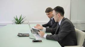Jeunes hommes travaillant, utilisant l'ordinateur portable et le comprimé dans le bureau moderne banque de vidéos