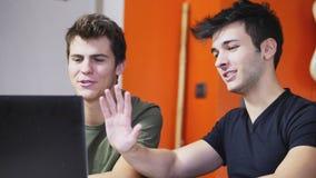 Jeunes hommes videochatting sur le PC d'ordinateur portable Photos libres de droits