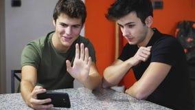 Jeunes hommes videochatting sur le PC d'ordinateur portable Image stock