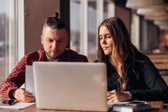 Jeunes indépendants homme et femme s'asseyant dans un café et travaillant pour un ordinateur portable photographie stock