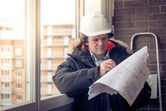 Jeunes ingénieurs employant la plume au papier de modèle pour examiner la structure de la maison avant de la présenter au photo libre de droits