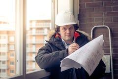 Jeunes ingénieurs employant la plume au papier de modèle pour examiner la structure de la maison avant de la présenter au photos libres de droits