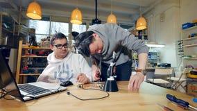Jeunes ingénieurs enthousiastes travaillant dans le studio moderne, faisant à 3d le bras bionique banque de vidéos