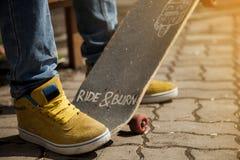 Jeunes jambes de planchiste faisant de la planche à roulettes au skatepark dehors Images stock