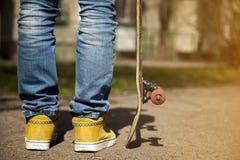 Jeunes jambes de planchiste faisant de la planche à roulettes au skatepark dehors Photo libre de droits