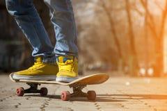 Jeunes jambes de planchiste faisant de la planche à roulettes au skatepark dehors Photos libres de droits