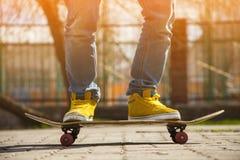 Jeunes jambes de planchiste faisant de la planche à roulettes au skatepark dehors Photo stock