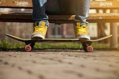 Jeunes jambes de planchiste faisant de la planche à roulettes au skatepark dehors Image stock