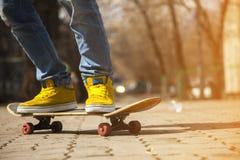 Jeunes jambes de planchiste faisant de la planche à roulettes au skatepark dehors Images libres de droits