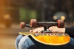 Jeunes jambes de planchiste faisant de la planche à roulettes au skatepark dehors Image libre de droits