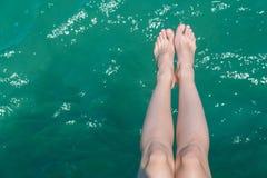 Jeunes jambes femelles accrochant au-dessus de l'eau de mer Photo stock