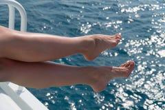 Jeunes jambes femelles accrochant au-dessus de l'eau de mer Photo libre de droits
