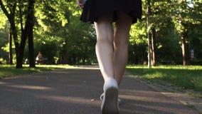 Jeunes jambes femelles marchant en parc banque de vidéos
