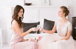 Jeunes jeune mariée et demoiselle d'honneur de sourire célébrant le jour du mariage Image stock