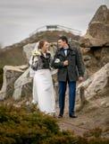 Jeunes jeunes mariés heureux marchant aux collines au jour froid Image stock