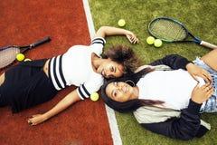 Jeunes jolies amies accrochant sur le court de tennis, stylis de mode Images stock