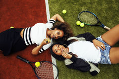 Jeunes jolies amies accrochant sur le court de tennis, stylis de mode Images libres de droits