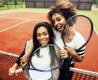 Jeunes jolies amies accrochant sur le court de tennis, stylis de mode Photographie stock