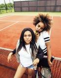 Jeunes jolies amies accrochant sur le court de tennis, stylis de mode Photo libre de droits