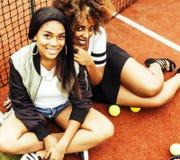 Jeunes jolies amies accrochant sur le court de tennis, stylis de mode Image stock