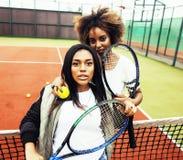 Jeunes jolies amies accrochant sur le court de tennis, stylis de mode Photographie stock libre de droits