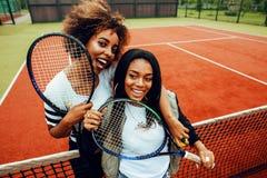 Jeunes jolies amies accrochant sur le court de tennis, stylis de mode Photos stock