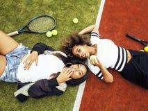 Jeunes jolies amies accrochant sur le court de tennis, stylis de mode Image libre de droits