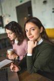 Jeunes jolies femelles travaillant avec les notes et l'ordinateur portable en café Photographie stock