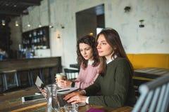 Jeunes jolies femelles travaillant avec les notes et l'ordinateur portable en café Photos stock