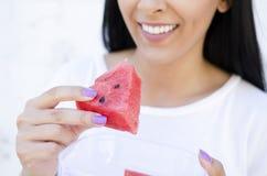 Jeunes jolies femmes tenant une tranche de pastèque et de sourire images stock