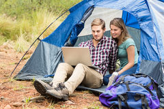 Jeunes jolis couples de randonneur se reposant dans une tente regardant l'ordinateur portable images libres de droits