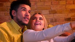 Jeunes jolis couples de type africain et de fille caucasienne parlant dans le videochat sur le comprimé étant joyeux à la maison clips vidéos