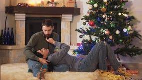 Jeunes jolis couples se trouvant à l'arbre de Noël ensemble An neuf et concept de No?l banque de vidéos