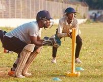 Jeunes joueurs de cricket pratiquant dans une photo unique de champ images stock