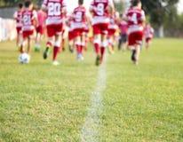 Jeunes joueurs de football courant dans des chemises rouges et blanches images stock