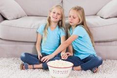 Jeunes jumeaux mangeant du maïs éclaté se reposant sur un tapis Photo libre de droits