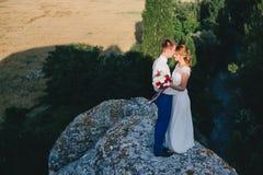 Jeunes juste ménages mariés heureux posant sur le dessus de la montagne Photos stock