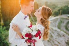 Jeunes juste ménages mariés heureux posant sur le dessus de la montagne Photos libres de droits