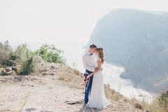 Jeunes juste ménages mariés heureux posant sur le dessus de la montagne Image libre de droits