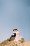 Jeunes juste ménages mariés heureux se reposant sur le dessus de la montagne Jour du mariage Images libres de droits