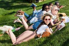 Jeunes livres de lecture multi-ethniques d'étudiants tout en se trouvant sur l'herbe verte en parc Photos stock