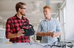 Jeunes lotisseurs discutant sur de nouveaux verres de réalité virtuelle Images libres de droits